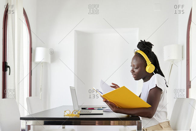 Businesswoman wearing headphones reading book at desk in home office
