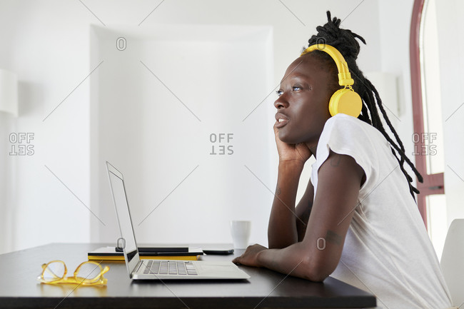 Thoughtful businesswoman with laptop on desk wearing headphones while sitting at home