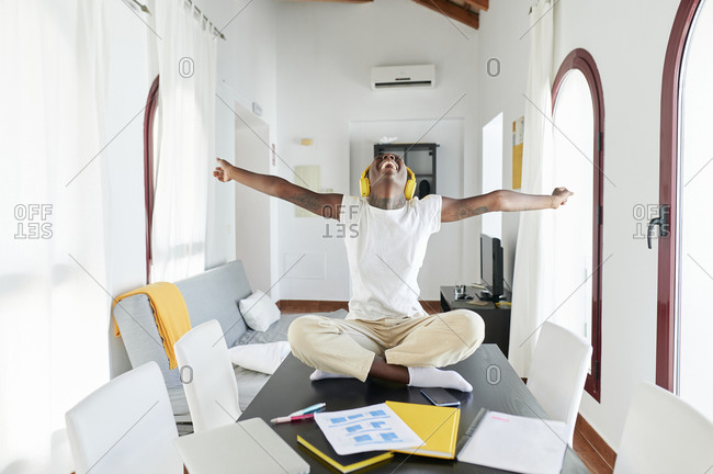 Businesswoman with arms outstretched listening music while sitting on desk at home