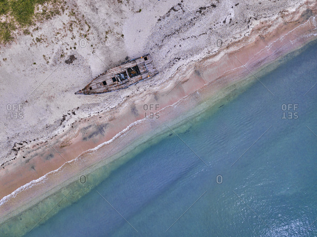 Aerial view of abandoned boat deteriorating on sandy coastal beach of Lukin bay