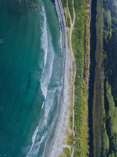 Aerial view of isthmus and dirt road stretching along coast of Krabbe Peninsula
