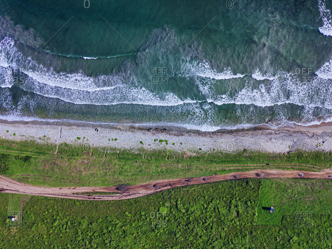 Aerial view of dirt road stretching along coastline of Krabbe Peninsula