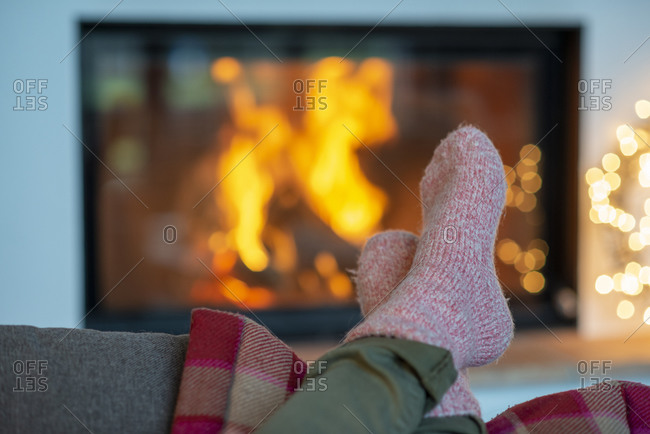 Legs of young woman wearing socks relaxing against fireplace at home