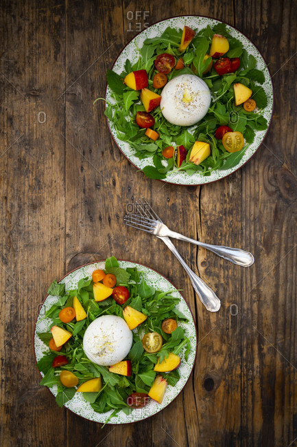 Two plates of fresh vegetarian salad with tomatoes- basil- arugula- nectarines- lemon balm and burrata cheese