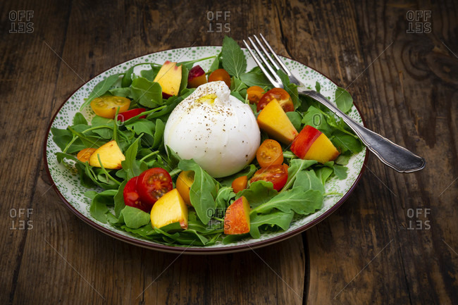 Plate of fresh vegetarian salad with tomatoes- basil- arugula- nectarines- lemon balm andburratacheese