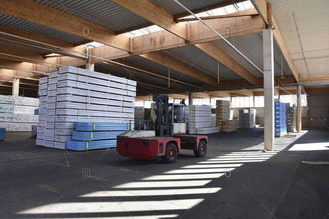 Forklift and stacked planks inside lumberyard warehouse