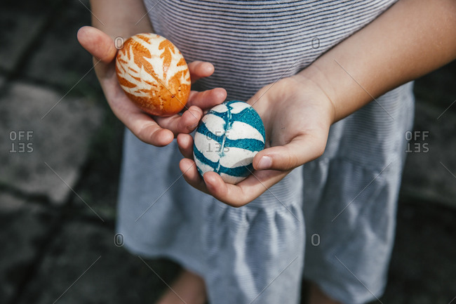Hands of baby girl holdingorganically coloredEaster eggs