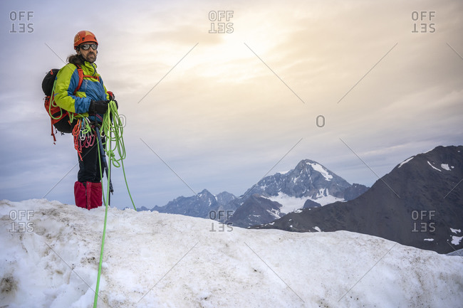 Mature man holding ropes while standing on snowcapped mountain against sky- Stelvio National Park- Italy
