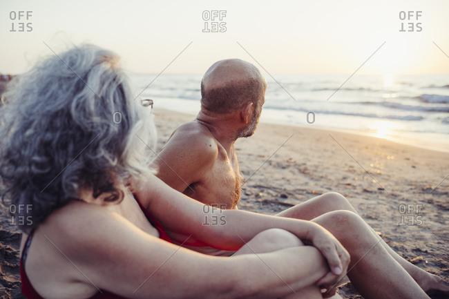Senior couple admiring sunset view while sitting at beach
