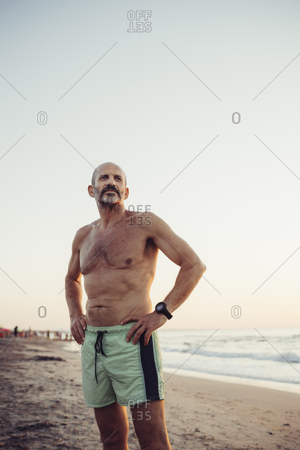 Man with hand on hip standing at beach