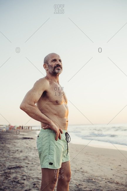 Man with hand on hip standing at beach during sunset