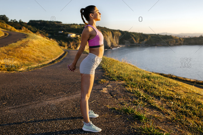 Young woman stretching hands while standing on cliff against clear sky during sunset