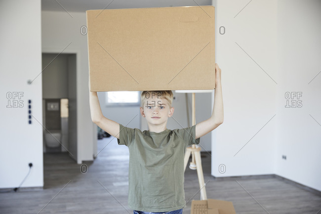Little boy carrying cardboard box on head