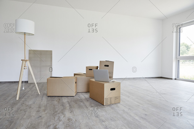 Interior of modern room with cardboard boxes- electric lamp and laptop