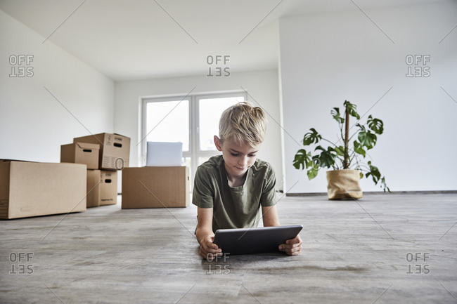 Boy lying down while playing on digital tablet in new house