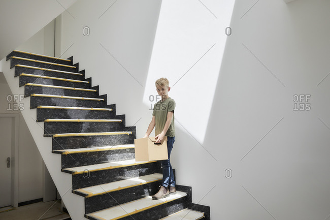 Cute little boy standing on staircase while holding cardboard box