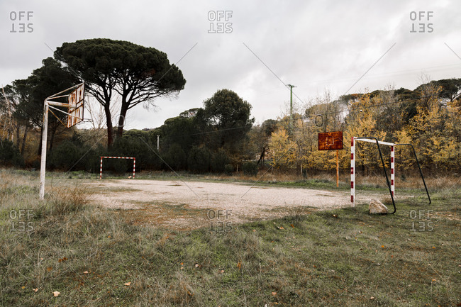 Small abandoned sports field with goals and basketball hoops