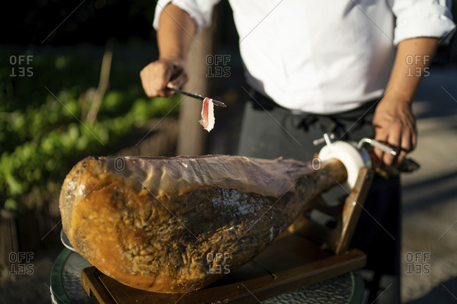 Close-up of male chef with ham on table standing outdoors
