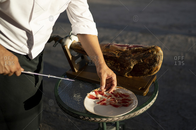 Male chef cutting slices of ham on table while standing outdoors