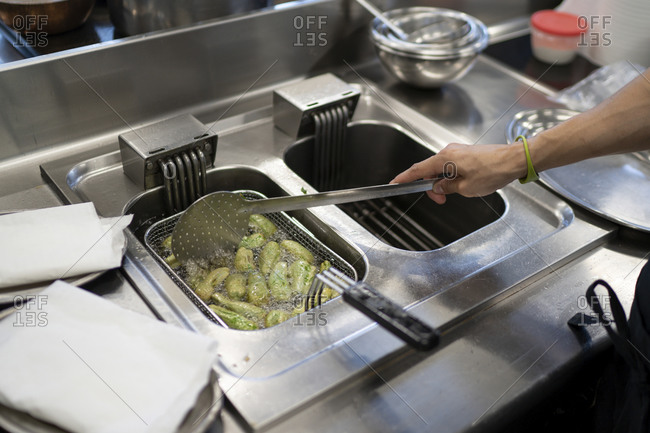 Male chef cooking jalapeno peppers in deep fryer at commercial kitchen
