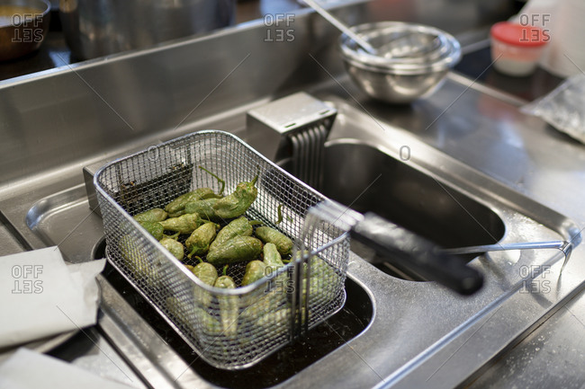 Jalapeno peppers in basket on deep fryer at commercial kitchen