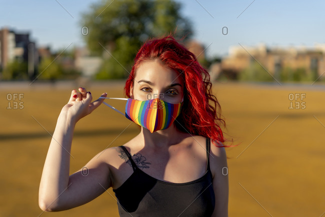 Redhead woman wearing multi colored face mask on sunny day