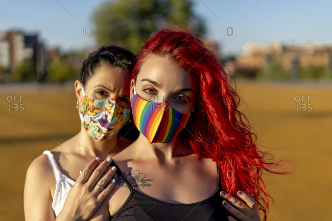 Friends wearing multi colored face mask while standing outdoors on sunny day
