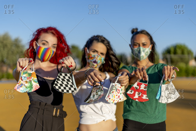 Friends holding multi colored face mask while standing outdoors