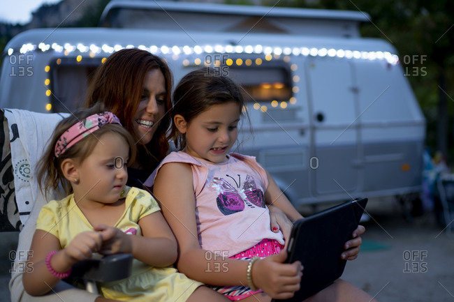Smiling mother with daughters using digital tablet while sitting against motor home at dusk