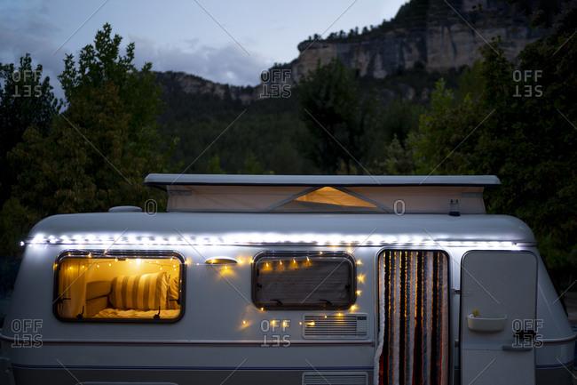 Illuminated motor home against mountain at dusk
