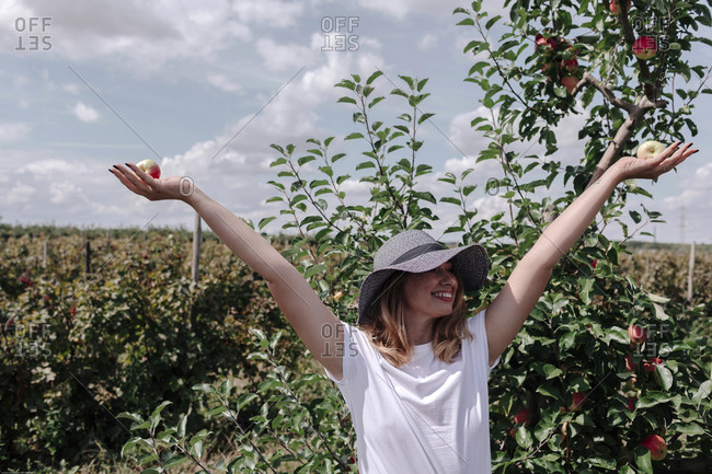 Carefree woman wearing hat with arms raised holding apples while standing in orchard