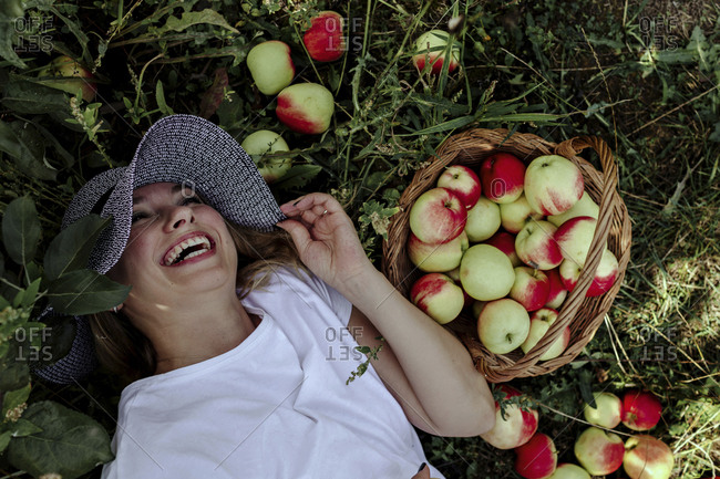 Mid adult woman wearing hat laughing while lying by apples on land in orchard