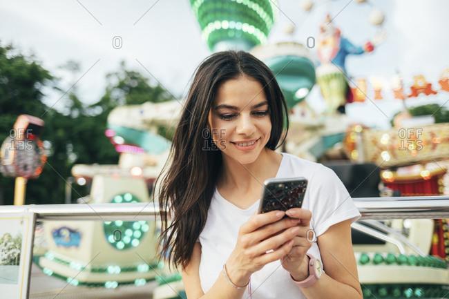Smiling beautiful woman using smart phone at amusement park
