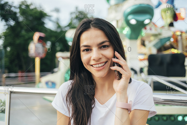 Close-up of smiling woman talking over smart phone at amusement park