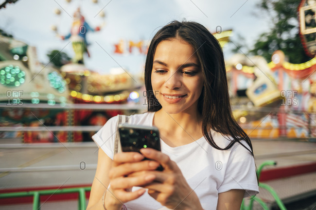 Close-up of beautiful woman using mobile phone at amusement park