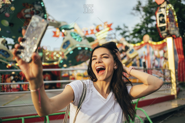 Cheerful young woman with hand in hair taking selfie at amusement park