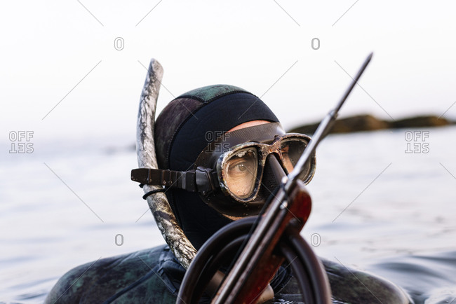 Close-up of mature man wearing scuba mask with harpoon swimming in sea