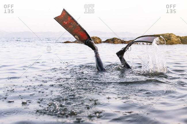 Legs of man wearing flippers diving in sea against clear sky