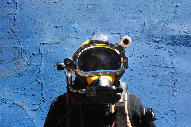 Close-up of male instructor wearing diving suit standing against blue wall