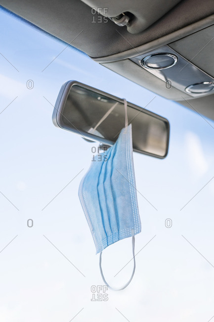 Close-up of face mask hanging on rear-view mirror in car