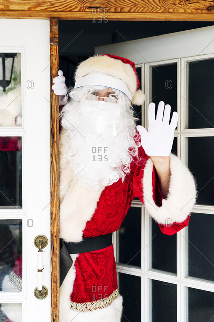 Man wearing Santa Claus costume showing stop sign while standing at entrance of house