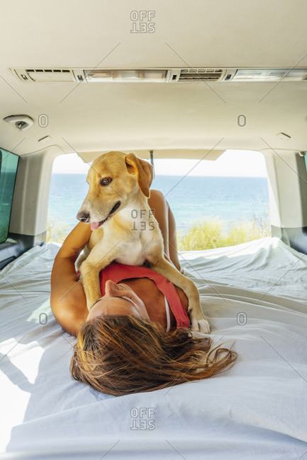 Woman with dog lying on bed in motor home