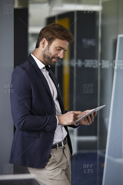 Businessman using digital tablet while standing at office