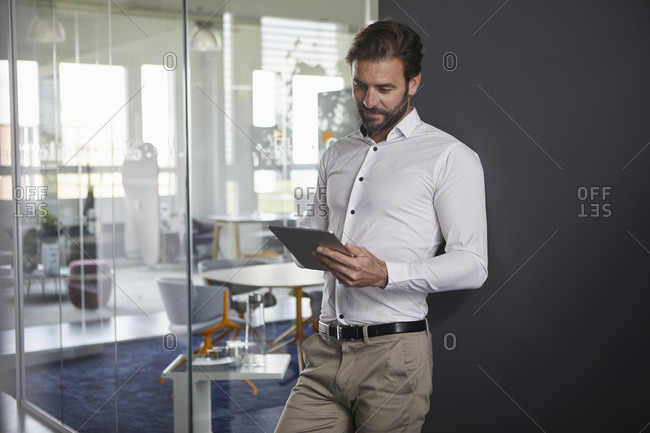 Businessman using digital tablet while leaning on wall at office