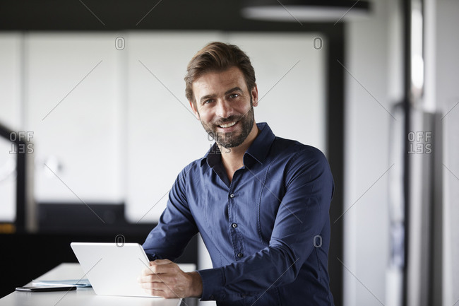 Smiling businessman using digital tablet while standing at desk in office