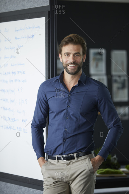 Smiling businessman standing with hands in pockets in office