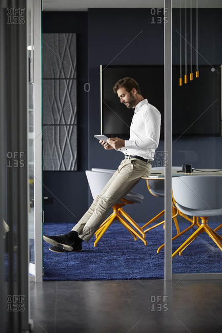 Businessman using digital tablet while sitting on table in office