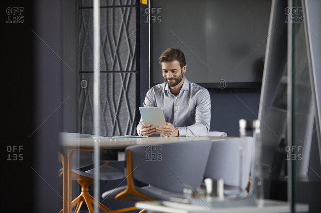Smiling businessman using digital tablet while sitting in office