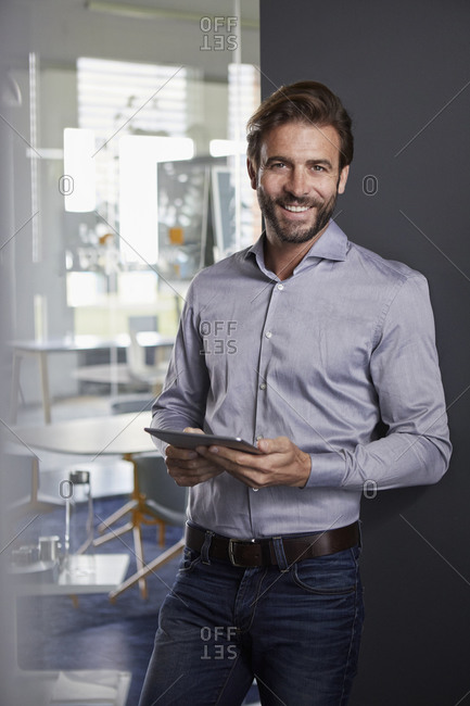 Smiling businessman using digital tablet while leaning on wall