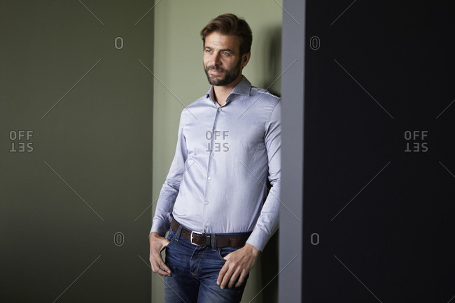 Businessman with hands in pockets standing against green wall